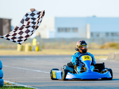 A kart driver passing the checkered flag at high speed while enjoying outdoor karting in Barcelona.