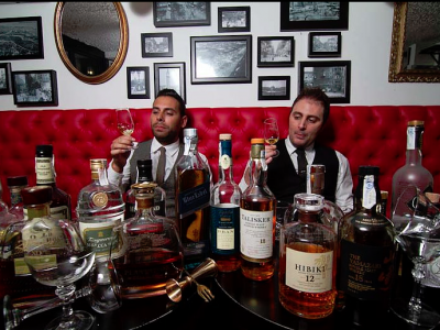 Two well-dressed men in an old-style themed bar enjoying a whiskey tasting masterclass in Barcelona.