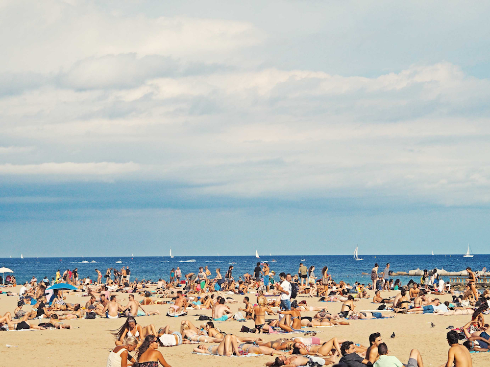 A shot of people enjoying the sun on the beach in Barcelona.