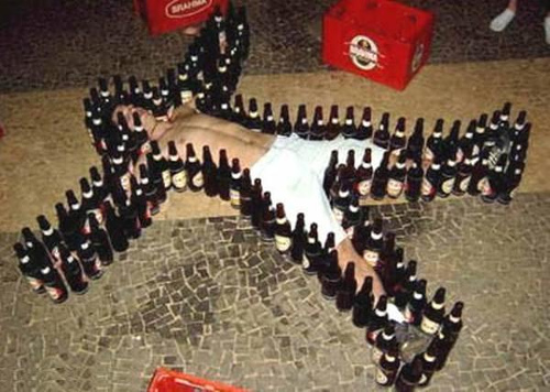 A photo of a drunk man laying on the ground surrounded by beer bottles.