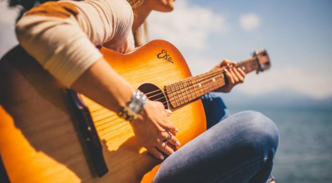 A photo of a person sitting with an acoustic guitar in front of the sea.
